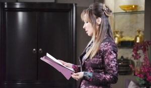 kate reads some document in Salem Inn hotel room
