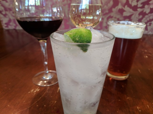 Soda with a Lime in front of Wine and Beer