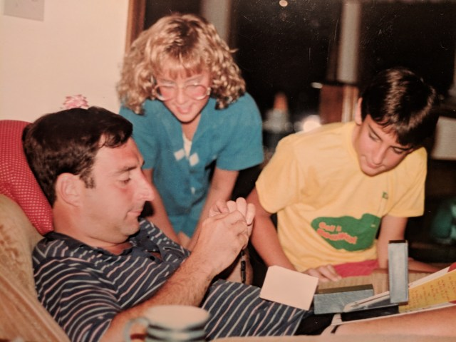 My dad helps with a school project while my sister watches (early 1980s).