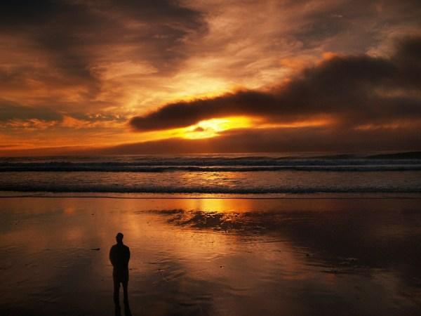человек смотрит на закат