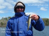 A smiling angler holding his catch of the day, a juvenile lake trout.