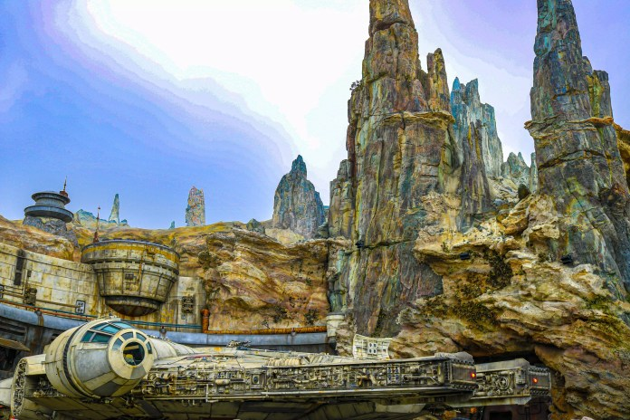 The sun peaks through the misty clouds beyond Black Spire Outpost's Spaceport at Star Wars: Galaxy's Edge.