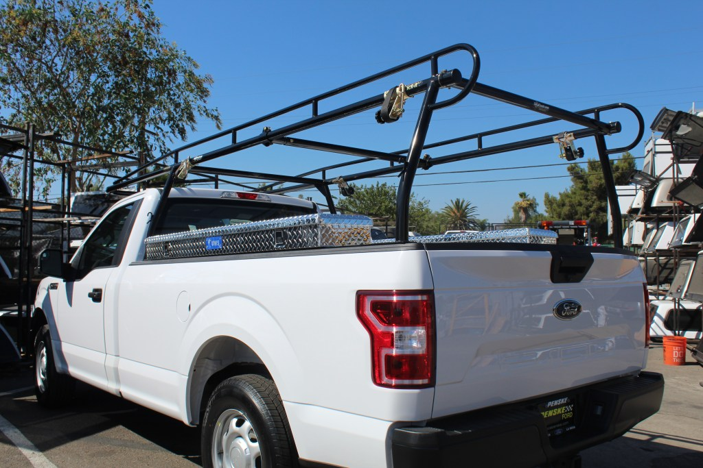 Standard Rack It 1000 Series lumber rack with installed rack straps, center bar, and side tool boxes.