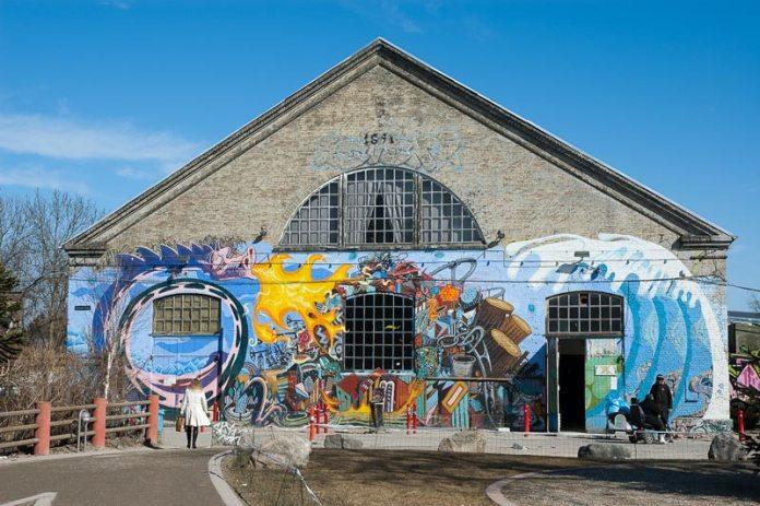 """""""Den Grå Hal"""" Christianias største lokale, som lægger hus til koncerter, udstillinger og f.eks. fællesmøder. Den Grå Hal er en gammel ridehal fra 1891. Den måler 47 x 19 meter og der er 16 meter til første kip på tagkonstruktionen. Kulturarvsstyrelsen fredede bygningen i 2007. Kilde: https://www.christiania.org/find/den-gra-hal/"""