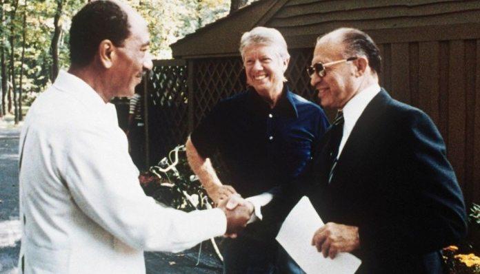Håndslaget i Camp David: Den zionistiske forbryder Begin med Egyptens præsident Anwar Sadat (de fik Nobels Fredspris i 1978. I baggrunden the fat cat, den amerikanske præsident Jimmy Carter. September 1978. Source: US govt. archives. Photo: ukendt. Public Domain