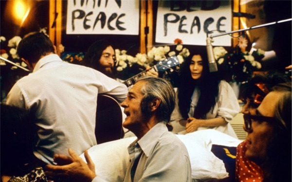 """Recording """"Give Peace a Chance"""". Left to right: Rosemary Leary ( face not visible), Tommy Smothers (with back to camera), John Lennon, Timothy Leary, Yoko Ono, Judy Marcioni and Paul Williams, Date: 1969. By Roy Kerwood - Originally uploaded to English Wikipedia by Roy Kerwood, CC BY 2.5, https://commons.wikimedia.org/w/index.php?curid=856687"""