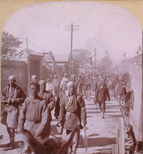 Company of Boxers, Tien-Tsin, China. Group of men walking down street. 1901. Source: Library of Congress, Prints & Photographs Division, LC-USZC4-3917. This is the left image of a stereographic view. Author: Stereo copyrighted 1901 by Whiting View Company. Public Domain. (Se the picture in the top of the page)