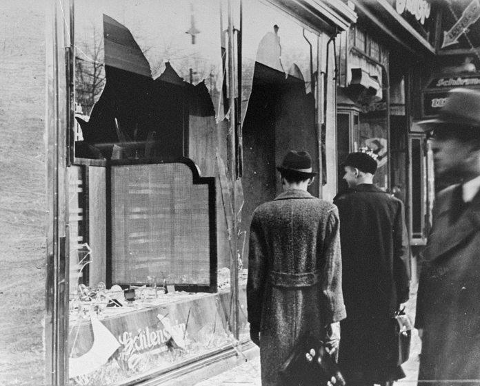 Berlin: Tyskere passerer forbi et smadret vindue for en jødisk ejet forretning, der blev ødelagt under Krystalnatten. Source: USHMM, courtesy of National Archives and Records Administration, College Park. Nov 10, 1938