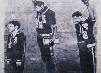 Graffiti on house wall in Newtown, Australia - The house might be demolished now. Tommie Smith (center) and John Carlos (right) showing the raised fist on the podium after the 200m in the 1968 Summer Olympics. Silver medallist Peter Norman from Australia (left) joins them in wearing Olympic Project for Human Rights badges. (CC BY 2.0)