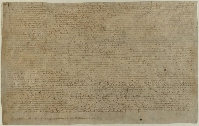 """The Magna Carta (originally known as the Charter of Liberties) of 1215, written in iron gall ink on parchment in medieval Latin, using standard abbreviations of the period, authenticated with the Great Seal of King John. The original wax seal was lost over the centuries.[1] This document is held at the British Library and is identified as """"British Library Cotton MS Augustus II.106"""". One of four known surviving 1215 exemplars of Magna Carta. Original authors were the barons and King John of England. Uploaded by Earthsound. Public Domain."""
