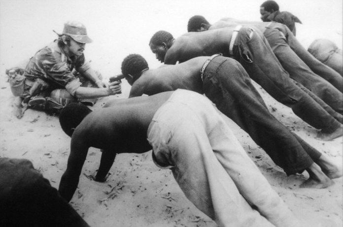 Anti-Guerrilla Operationer i Rhodesia. Sorte tortureres for at få dem til at fortælle om guerilla aktiviteter. 1977. Feature Photography, J. Ross Baughman, Associated Press 1978 Pulitzer Prize. (CC BY 2.0)