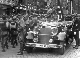 Parade of SA troops past Hitler, Nuremberg 1935. In the car with Hitler: the Blutfahne, behind the car: SS-man en:Jakob Grimminger the carrier of the Blutfahne flag. From the Reichsparteitag der NSDAP 10th-16th September 1935. Author: Charles Russell Collection, NARA. Public Domain. Source: Wikimedia Commons