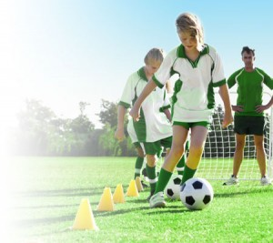 youth soccer players practicing with pylons looked on by their coach