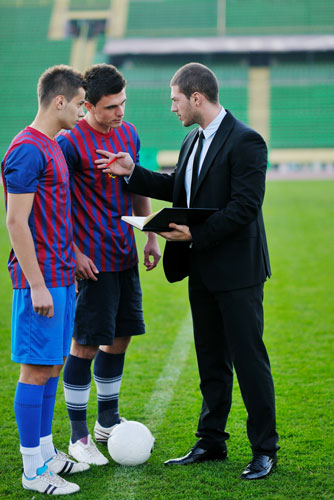 Coach talking to two star soccer players