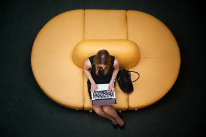 Young female sitting on yellow coach working on laptop in public wifi area, typing, top view