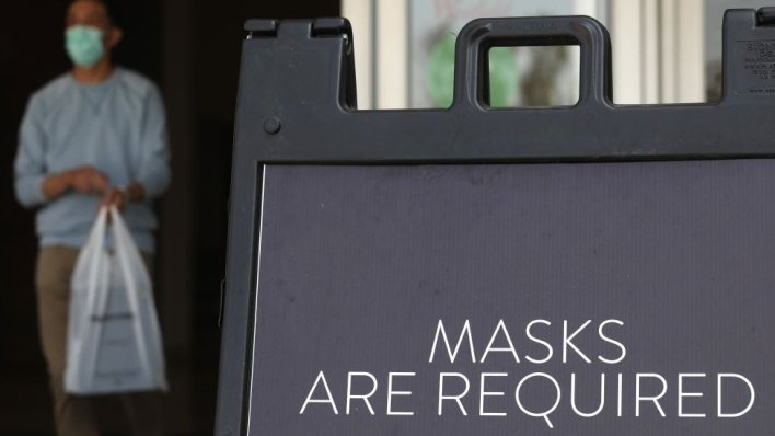 A sign tells store customers to wear masks to prevent the spread of Covid-19