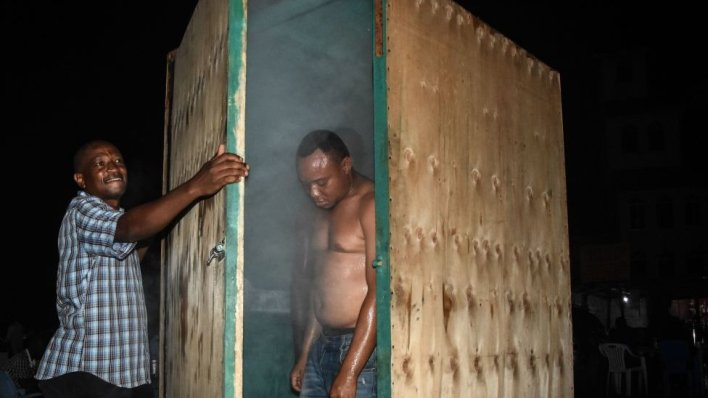 A man leaves a steam inhalation booth installed by a herbalist in Dar es Salaam, Tanzania, on 22 May 2020