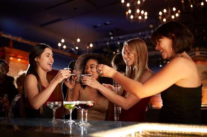 four women friends standing and drinking at night in a bar