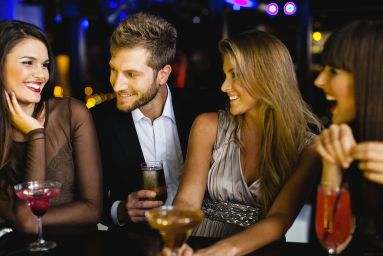 group of three beautiful women and one man sharing wine while laughing at bar