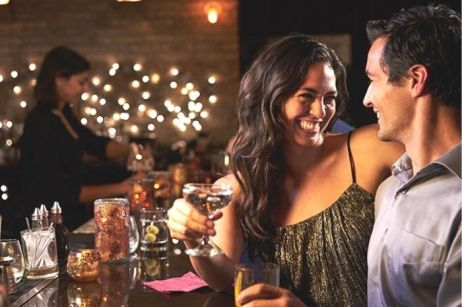 man and woman cuddling on date at a bar while looking into each others eyes and smiling while holding wine with woman and fairy lights in back ground