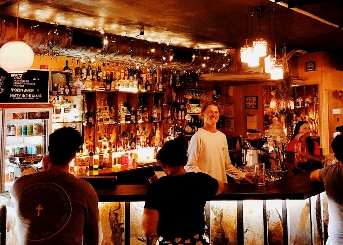 bar tender with white shirt smiling in hidden fiftyfive basement bar with customers buying beer and spirits on back shelves