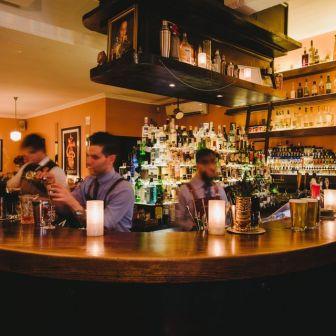 bar tenders behind counter making drinks at lily blacks