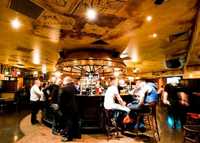 patrons being served guinness and whiskies in P.J.O'Brien's circular side bar in Southbank Irish Pub
