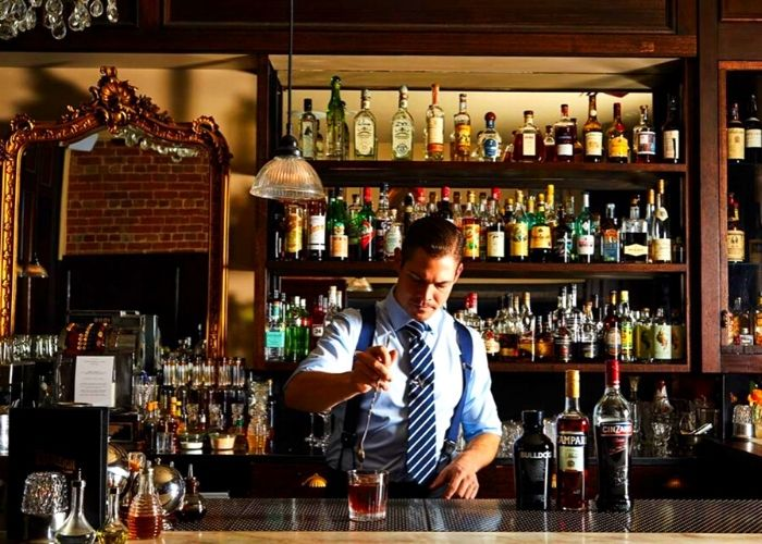 male bar tender with blue shirt and tie making drink at the Everleigh in Fitzroy