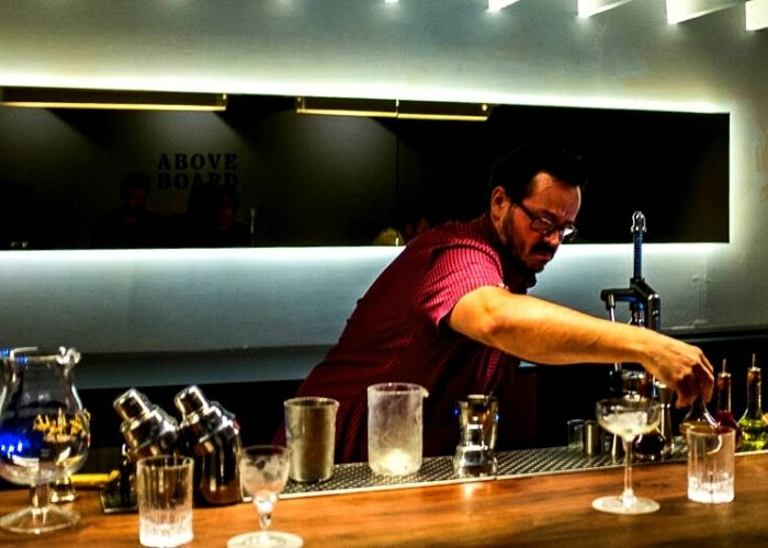 hayden scott in red shirt and glasses making cocktails at collingwood bar above board