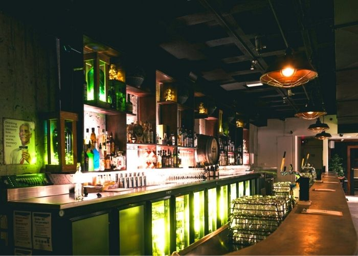 inside of black rabbit melbourne nightclub with green lights and alcohol bottles and wine glasses at bar