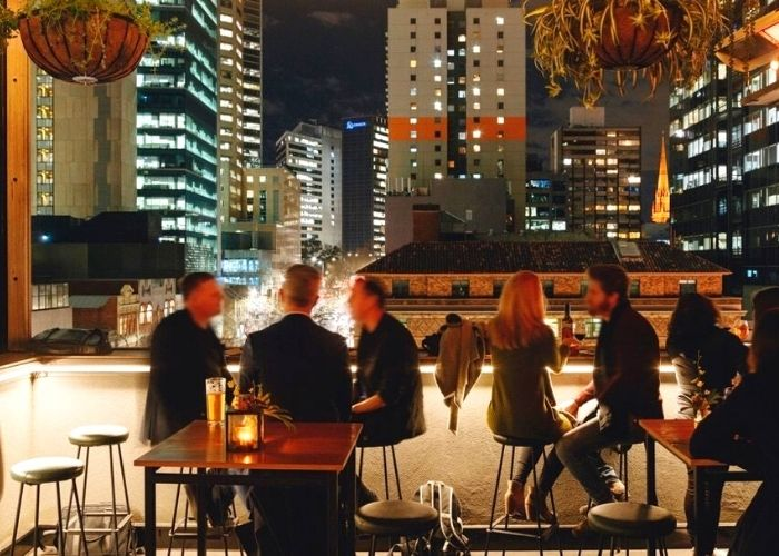 people seated at night on stools at bomba outdoor tappas bar with cbd building lights in back ground on 103 lonsdale street