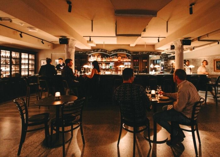two men seated at small candle lit table in dessous basment wine bar on flinders lane