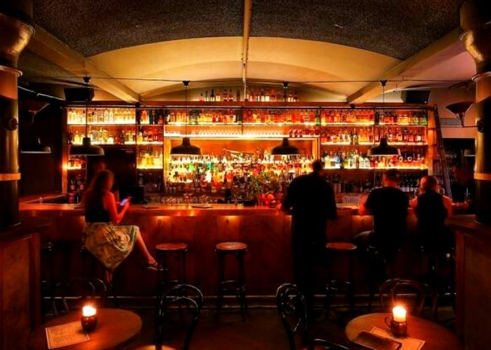 dimly lit basement venue in CBD with 4 people seated on stools at beneath driver lane bar