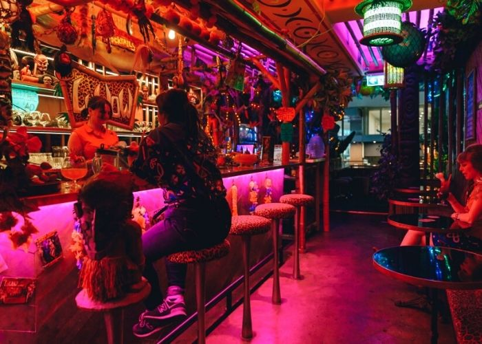 two women seated in colourful south pacific themed luwow tiki bar ordering drinks from bar tender