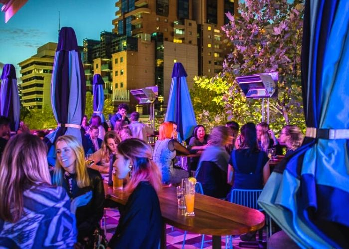 outdoor party with blue umbrellas at night at Good Havens rooftop bar with cbd in background