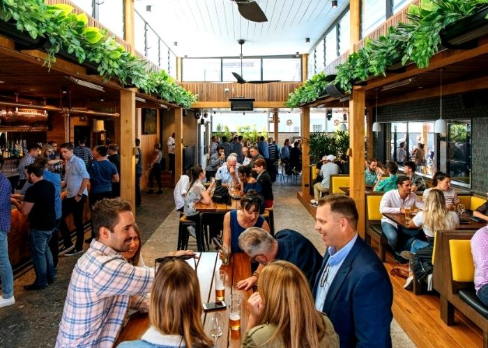 large party function at the albion rooftop with people drinking in booths and at tables with over hanging greenery plants