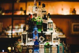 stack of gin, vodka and whiskey bottles at lily black CBD bar