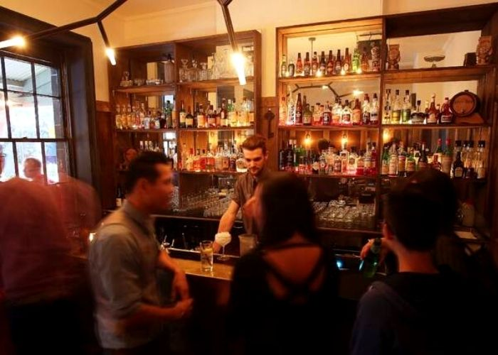 inside upstairs pub of loch & Key on 34 franklin street. bar tender pouring drinks for customers at cocktail and whisky and craft beers on back shelves