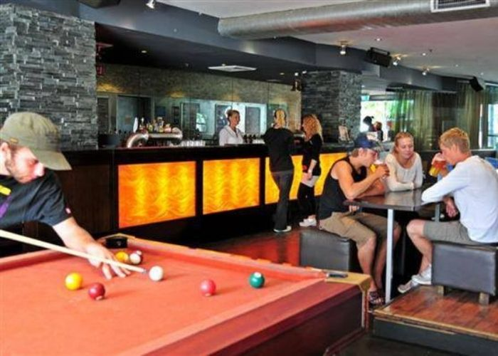 man with brown cap playing pool with three people seated drinking at table in back ground at cbd industry bar and lounge