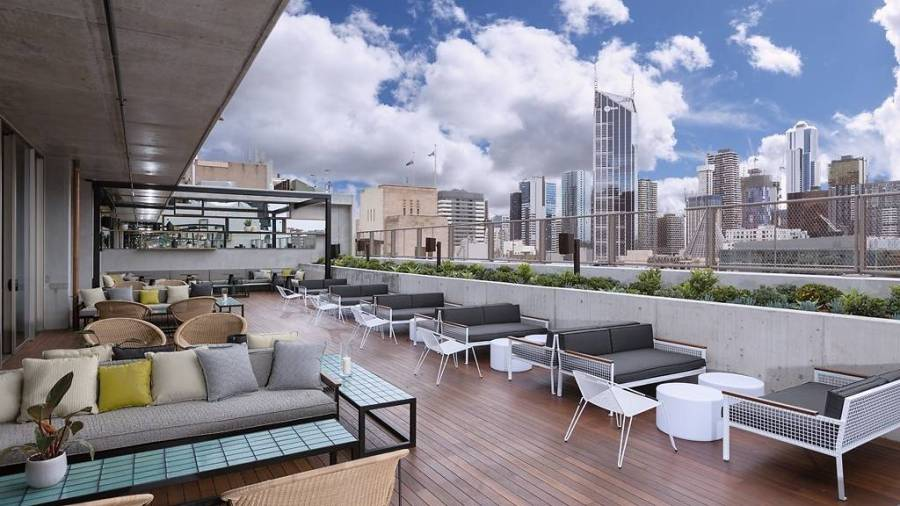 impressive cbd views during the day off QT rooftop lush beer garden and couches under blue skies