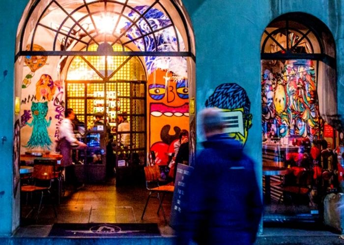 bright art drizzled street view of bar ampere on russell place at night with waiter and patrons dining inside venue