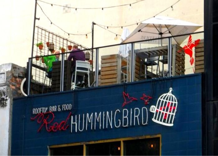 Street view of the red hummingbird rooftop with chairs and fair lights