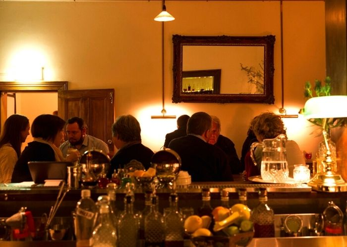 patrons dining at romeo lane, an intimate dimly lit table service basement cocktail bar on Crossley Street