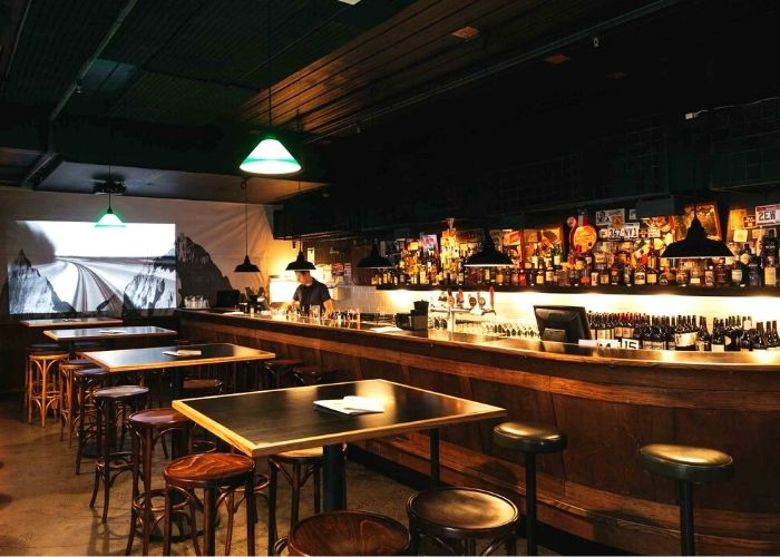 inside of saving grace bar with staff member mixing drinks with tables and bar stools