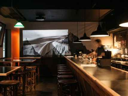 empty saving grace venue with bar tender black bar stools and downlights