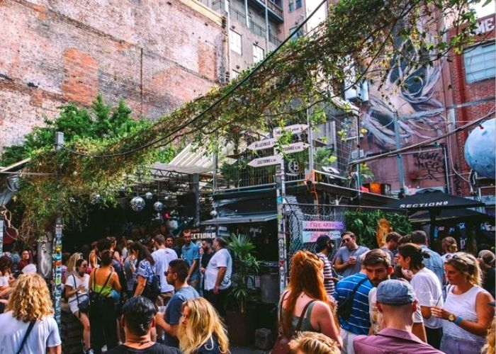 large group of people at outdoor bar during the day at section 8 container bar with graffiti covered walls on tattersalls lane cbd