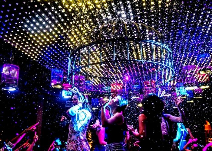 beautiful women dancing at spice market nightclub bird cage dance floor with laser lights and confetti