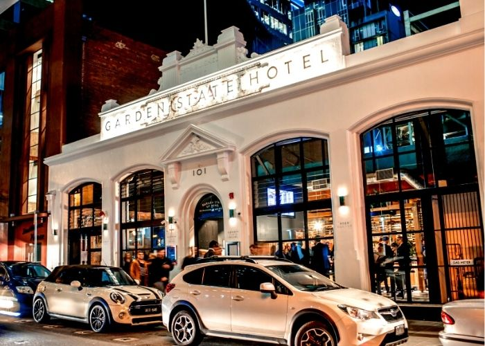 outside street view at night of garden state hotel on flinders lane with crowds drinking and white cars parked along street