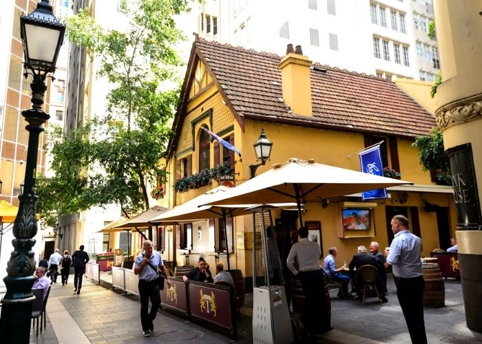 outside street view of the historic mitre tavern and beer garden during the day with patrons enjoying drinking on 5 Bank place in the city cbd