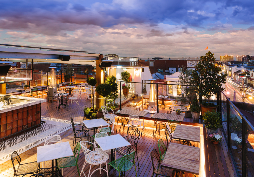 panoramic city views and blue sky from the provincial rooftop with deck chairs and tables in afternoon light